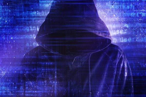 hooded person surrounded by cybersecurity networks